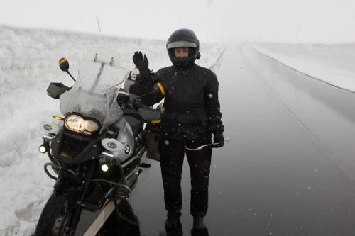 Ung kvinne og motorsykkel i sne